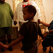 GREENVILLE, MS - September 3, 2005:  A family of evacuees, including 5-yr-old Ashton Cotton, from New Orleans gather and pray in a home donated to them by a friend of Dr. Ronald Myers on September 3, 2005. As a doctor and advocate for the poor, he is treating evacuees from New Orleans and other parts of Louisiana and Mississippi in shelters and at homes where the evacuees have taken up residence. His personal home and his in-laws home were severely damaged and all are living in a Ramada Inn...(Photo by Todd Bigelow/Aurora)..