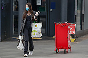 A girl carrying her shopping bags, wearing face protective mask and surgical gloves is seen walking near Tottenham Court Road underground station in central London on Monday, May 11, 2020. <br />