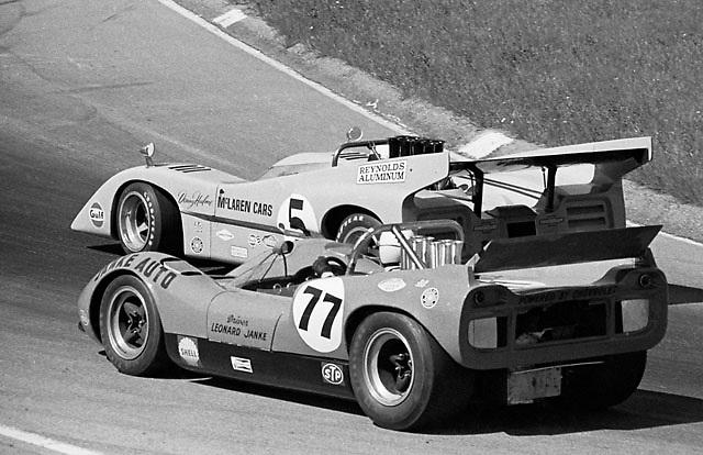 McLaren M1C of Leonard Janke (77) in 1970 Mosport Can-Am being overtaken at Moss Hairpin by McLaren M8D of Denny Hulme, illustrating rapid evolution of McLaren design; PHOTO BY Pete Lyons / www.petelyons.com