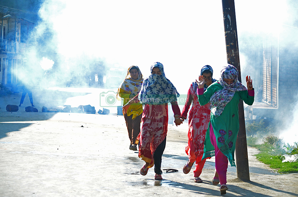 July 21, 2017 - India - Kashmiri muslim women run for safer places after Indian police teargassed the funeral of Tanveer Ahmad ,a tailor by profession in Beerwah some 40 kilometers from Srinagar the summer capital of Indian controlled Kashmir on July 21, 2017.  Tanveer Ahmad was killed after Indian army opened fire on protesters in the Beerwah area of central Kashmir's Budgam.Residents of the locality said the soldiers fired on worshippers after some stones hit the iron shutters of shops that were closed because of a general strike called by pro freedom leadership against the recent killings in Kashmir.However, police said that army opened fire after mistaking sound of firecrackers with grenade blast which lead to the killing of Tanveer. (Credit Image: © Faisal Khan/Pacific Press via ZUMA Wire)