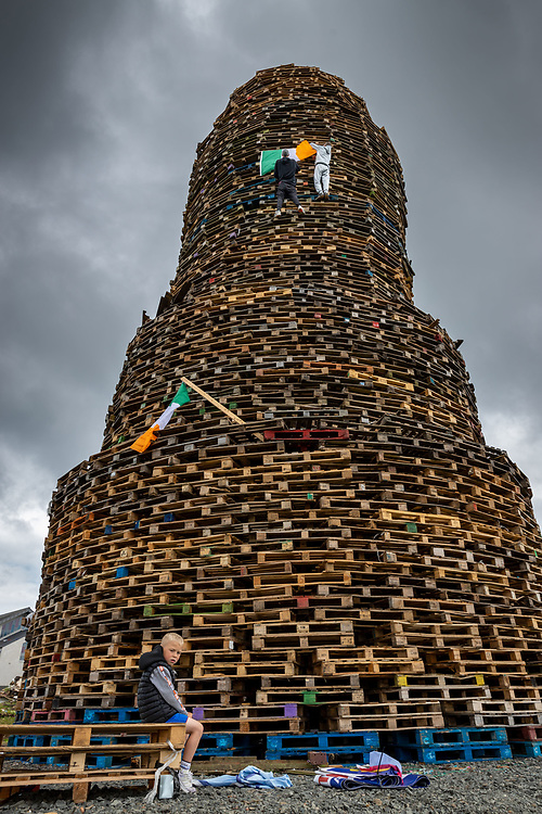 Two men climb the high bonfire in Larne, in order to fly the Irish Tricolour flag. In preparation of the midnight lighting of the massive fire. Belfast, NI, 2021.