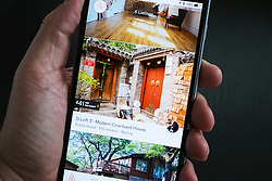 Airbnb holiday room booking app showing traditional courtyard house in Beijing for rent on an iPhone 6 plus smart phone