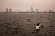 A Vietnamese man toting a polystyrene box fishes in West Lake at dusk, Hanoi, Vietnam, Southeast Asia