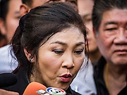 11 NOVEMBER 2016 - BANGKOK, THAILAND: YINGLUCK SHINAWATRA talks to reporters at a rice distribution sale in the Bangkok suburbs. Yingluck was deposed in a coup in 2014, has started selling rice directly to Thai consumers. She buys the rice from farmers at market prices and then sells it to urban consumers at the price she paid. She said she's doing it to help out farmers, who are trying to deal with depressed prices. Yingluck is facing prosecution on corruption related charges going back to a rice price support scheme her government used to try to help farmers in 2011 and 2012. Even after the coup, she is still personally popular and hundreds of people showed up to see her at the rice distribution point at a mall in Samut Prakan province, in suburban Bangkok.   PHOTO BY JACK KURTZ