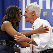 "First Lady Michelle Obama hugs Charlie Crist prior to his grassroots ""Commit to Vote"" rally at the Barnett Park Gymnasium in Orlando, Florida on Friday, Nov. 17, 2014. (AP Photo/Alex Menendez)"