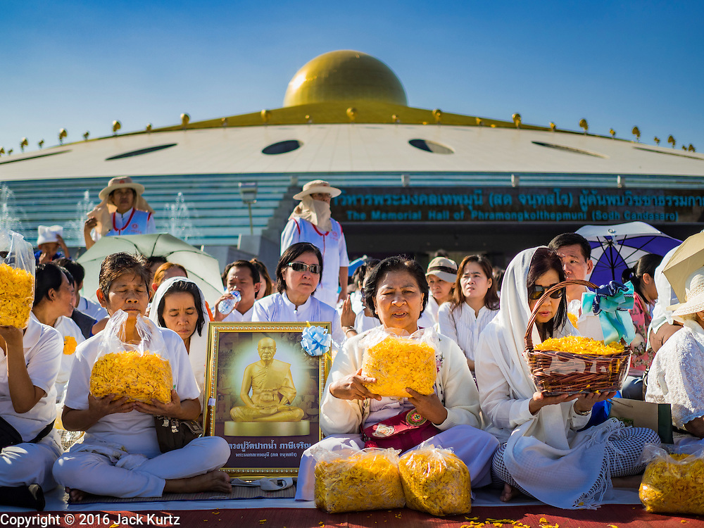 """02 JANUARY 2016 - KHLONG LUANG, PATHUM THANI, THAILAND:   People with a picture of the Abbot of Wat Phra Dhammakaya pray while they wait for the start of a mass pilgrimage of Buddhist monks at Wat Phra Dhammakaya on the first day of the 5th annual Dhammachai Dhutanaga (a dhutanga is a """"wandering"""" and translated as pilgrimage). More than 1,300 monks are participating pilgrimage through central Thailand. The purpose of the pilgrimage is to pay homage to the Buddha, preserve Buddhist culture, welcome the new year, and """"develop virtuous Buddhist youth leaders."""" Wat Phra Dhammakaya is the largest Buddhist temple in Thailand and the center of the Dhammakaya movement, a Buddhist sect founded in the 1970s. The monks are using busses on some parts of the pilgrimage this year after complaints about traffic jams caused by the monks walking along main highways.        PHOTO BY JACK KURTZ"""