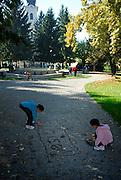 Children writing their names in gravel, Strossmayer Promenade (Strossmayerova setalista), town square park, with new Church of Saint Lawrence (Crkva Sveti Lovre) in background. Petrinja, Croatia