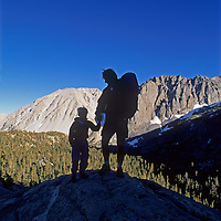 A father and son stand atop a granite dome in Big Pine Canyon in California's eastern Sierra Nevada.  Behind them are Slide Mountain and Temple Crag.