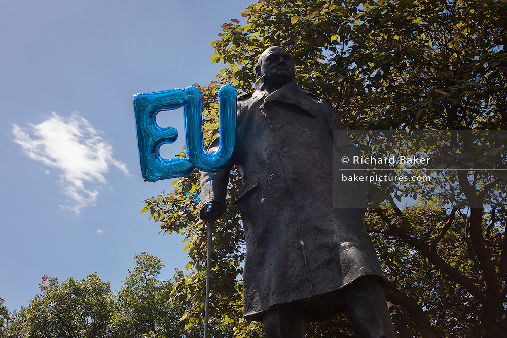 "As thousands of British voters march through London to protest against the referendum decision to leave the EU (Brexit), EU balloons are attached to the statue of Sir Winston Churchill, on 2nd July 2016, in London UK. Demonstrators at the ""March for Europe"" rally, which was organised on social media walked from Park Lane into the heart of the UK government in Westminster to send a message of dissatisfaction in the referendum result. More than 46.5 million people voted in the referendum on 23 June, which resulted in the UK voting by 51.9% to 49.1% to withdraw from the EU."