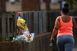 Flowers have been laid against a fence opposite the house where seven-year-old Joel Urhie died in a suspected arson attack on his home in Deptford in the early hours of Tuesday 7th August. London, August 08 2018.