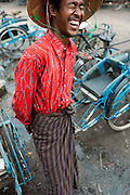 Shy, happy trishaw driver with big hat laughing and hiding from camera