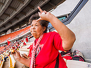 """A Red Shirt supporter dances to Thai country music during a Red Shirt rally in Bangkok. As many as 30,000 """"Red Shirts"""" are expected in Bangkok this week ahead of a Thai court ruling that could cause the collapse of the government of Yingluck Shinawatra, the Prime Minister. The Red Shirts are gathering in a suburban sports stadium before marching to the court. The Red Shirts are mostly farmers and rural Thais who support the Shinawatra government."""