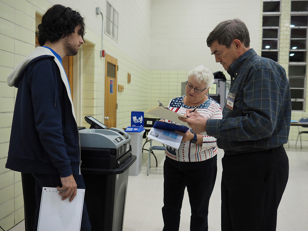 Election Chief and Poll workers review polling information after polls close on Election Day, November 5, 2019