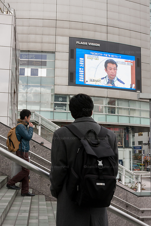 People watch video screens for news after a magnitude 9 earthquake and large tsunami hit the Tohoku region of north east Japan  on March 11th killing nearly 20,000 people and causing massive destruction along the whole coast, and a melt-down at the Fukushima Daichi nuclear power stationShinjuku, Tokyo, Japan March 16th 2011