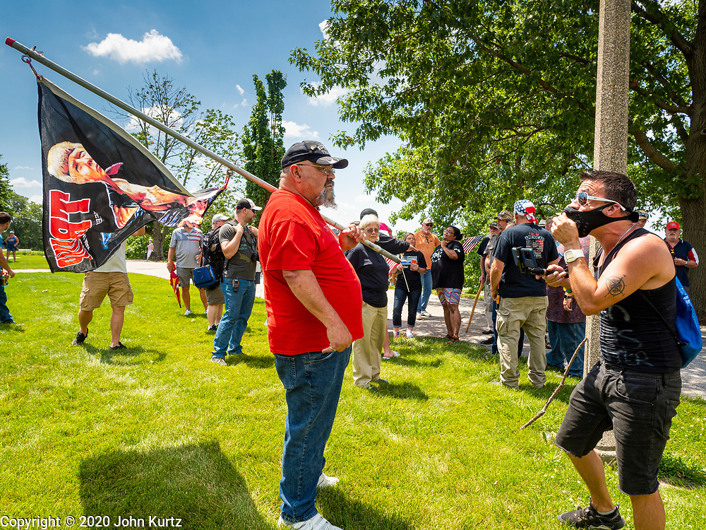 04 JULY 2020 - DES MOINES, IOWA: A member of Black Lives Matter (right) argues with Donald Trump supporters on the grounds of the Iowa State Capitol. Hundreds of people came to the grounds of the Iowa State Capitol to protest against and in favor of historic monuments on the capitol grounds. Several hundred people protested against a monument to Christopher Columbus and the stereotypical depiction of Native Americans on the capitol grounds. About 50 people came to the capitol to rally in support of the monuments. The protest against the monuments was organized by Seeding Sovereignty, a collective of indigenous women. The rally to defend the monuments was organized by an Iowa chapter of Three Percenters.     PHOTO BY JACK KURTZ