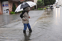 """Standing at the corner of W. San Luis St. and Cayuga St. in Salinas at 2:00 PM, resident Miguel Payan wonders at the volume of rain caused by Thursday's """"Pineapple Express"""" storm."""