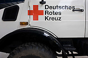 Deutsches Rotes Kreuz - DRK (German Red Cross) vehicle logos at their administrative HQ, 58 Carstennstrasse, Berlin. Ready for immediate loading into disaster zones, the equipment is stored near to where freight aircraft can fly anywhere in the world. The International Red Cross and Red Crescent Movement, with its 187 National Societies, is the world's largest humanitarian network. The German Red Cross is part of this universal community, which started 150 years ago to deliver comprehensive aid to people affected by conflict, disaster, sanitary emergencies, or social hardship, guided solely by their needs. Around four million volunteers and members support the Red Cross in Germany alone.
