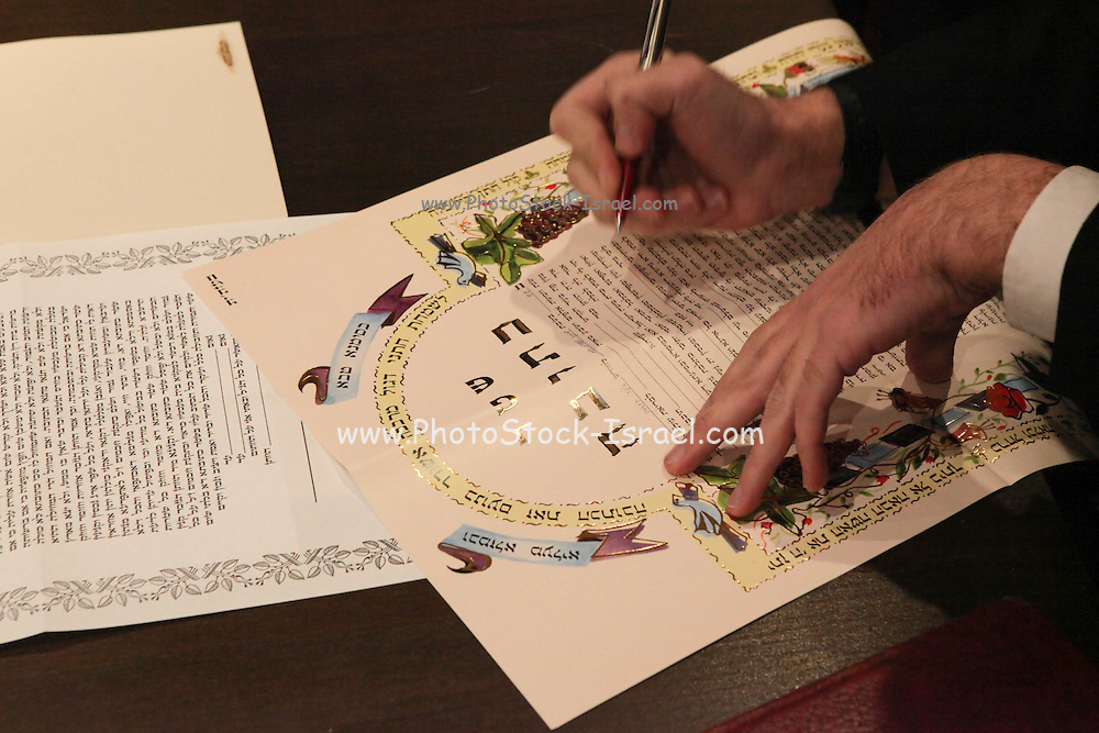 Traditional Jewish Wedding. Groom signs the ketubah before the marriage