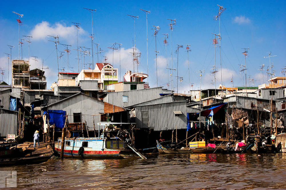 These squatter homes on the Mekong River in Chau Doc may not have indoor plumbing, but they are connected to the world via television. This image shows how Vietnam is embracing the global economy but with one foot still rooted in its past. Robert Dodge, a Washington DC photographer and writer, has been working on his Vietnam 40 Years Later project since 2005. The project has taken him throughout Vietnam, including Hanoi, Ho Chi Minh City (Saigon), Nha Trang, Mue Nie, Phan Thiet, the Mekong, Sapa, Ninh Binh and the Perfume Pagoda. His images capture scenes and people from women in conical hats planting rice along the Red River in the north to men and women working in the floating markets one the Mekong River and its tributaries. Robert's project also captures the traditions of ancient Asia in the rural markets, Buddhist Monasteries and the celebrations around Tet, the Lunar New Year. Also to be found are images of the emerging modern Vietnam, such as young people eating and drinking and embracing the fashions and music of the west.
