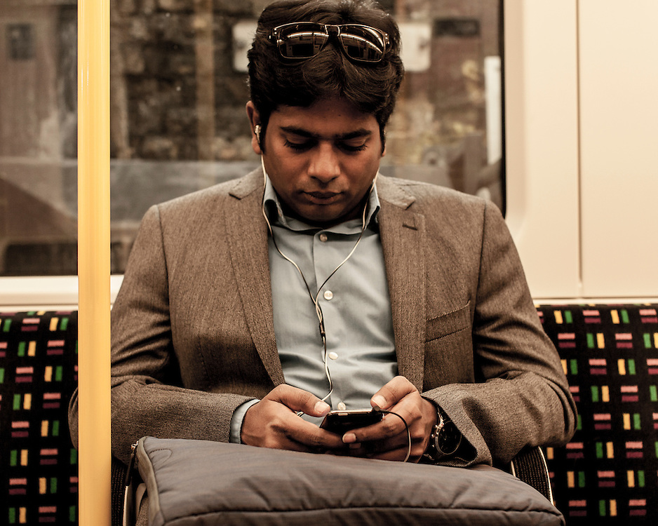 Asian Indian man texting on the phone on the London Underground