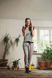 Young woman exercising with rope in living room, Munich, Bavaria, Germany