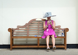 © Licensed to London News Pictures. 17/06/2014. Ascot, UK. A woman uses her mobile phone.  Day one at Royal Ascot 17th June 2014. Royal Ascot has established itself as a national institution and the centrepiece of the British social calendar as well as being a stage for the best racehorses in the world. Photo credit : Stephen Simpson/LNP