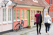Tourists in Overstraede cobbled street with painted houses and cobblestone  in Odense on Funen Island, Denmark