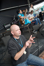 Man using sign language during stage performance by Sheema Mukherjee at the WOMAD (World of Music; Arts and Dance) Festival in reading; 2005,