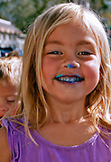 Cute Blonde Girl With Frosting On Her Nose And Mouth
