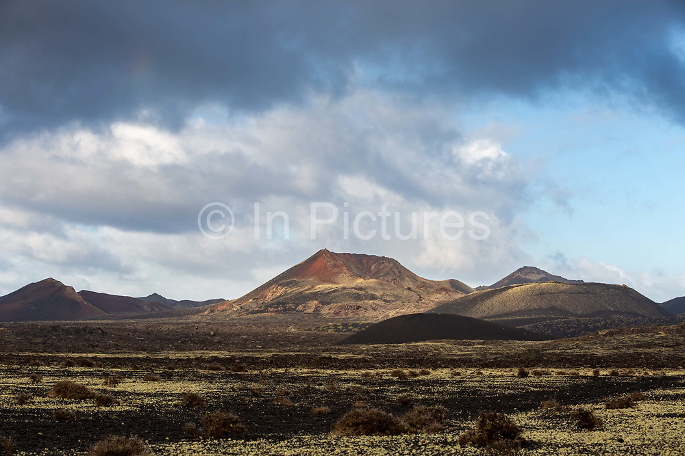 Volcanic peaks are illuminated by the morning sun on 27th November 2020 in Los Volcanes Natural Park in Lanzarote, Spain. The island was transformed by huge volcanic eruptions from 1731-36, which give it its unique dramatic landscape. .