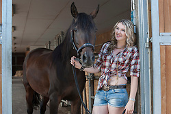 Young woman standing with her brown horse in stable and smiling, Bavaria, Germany