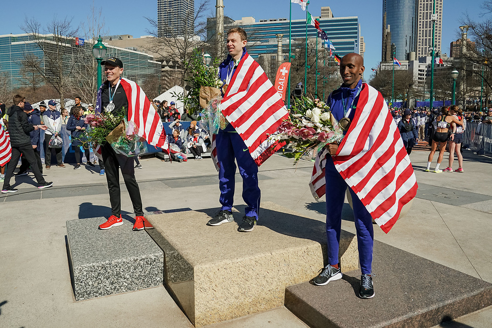 Galen Rupp (center), Jacob Riley (left) and Abdi Abdirahman (right) celebrate winning first, second, and third, respectively, during the 2020 U.S. Olympic marathon trials in Atlanta on Saturday, Feb. 20, 2020. Photo by Kevin D. Liles for The New York Times