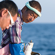Elder Hasegawa-san looking on as his son works on fishing lines