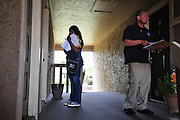 (L to R) Nekia Tillotson and Raul Moreno of the Dallas Police Department go door to door as a part of the new 10/70/20 program at The Lodge at Timberglen apartments in Dallas on Saturday, March 30, 2013. (Cooper Neill/The Dallas Morning News)