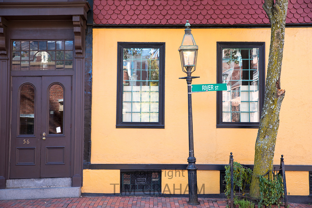 Brightly coloured home and old fashioned street lamp in River Street in the historic district of Boston, Massachusetts, USA