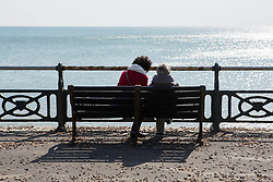 People look out to sea on the seafront in Brighton, East Sussex, as the UK continues in lockdown to help curb the spread of Coronavirus.