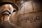 "A labyrinth of covered streets and alleys wind through the ancient mud brick city of Yazd, Iran. The graffiti on the wall says ""battle-axe""."