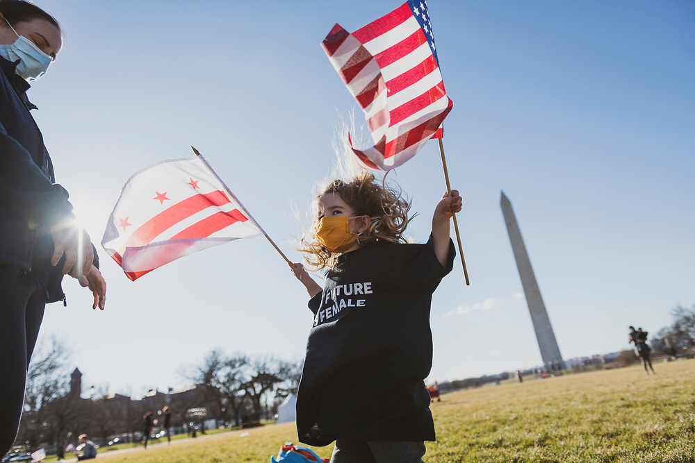 Washington DC, USA - January 21, 2021:  Reise Tuason, 3, enjoys a beautiful day with her mom Jennifer on the National Mall the day after the 59th Presidential Inauguration, playing with flags that had been used to decorate the mall for the event. The Tuasons drove from southern California for the inauguration.