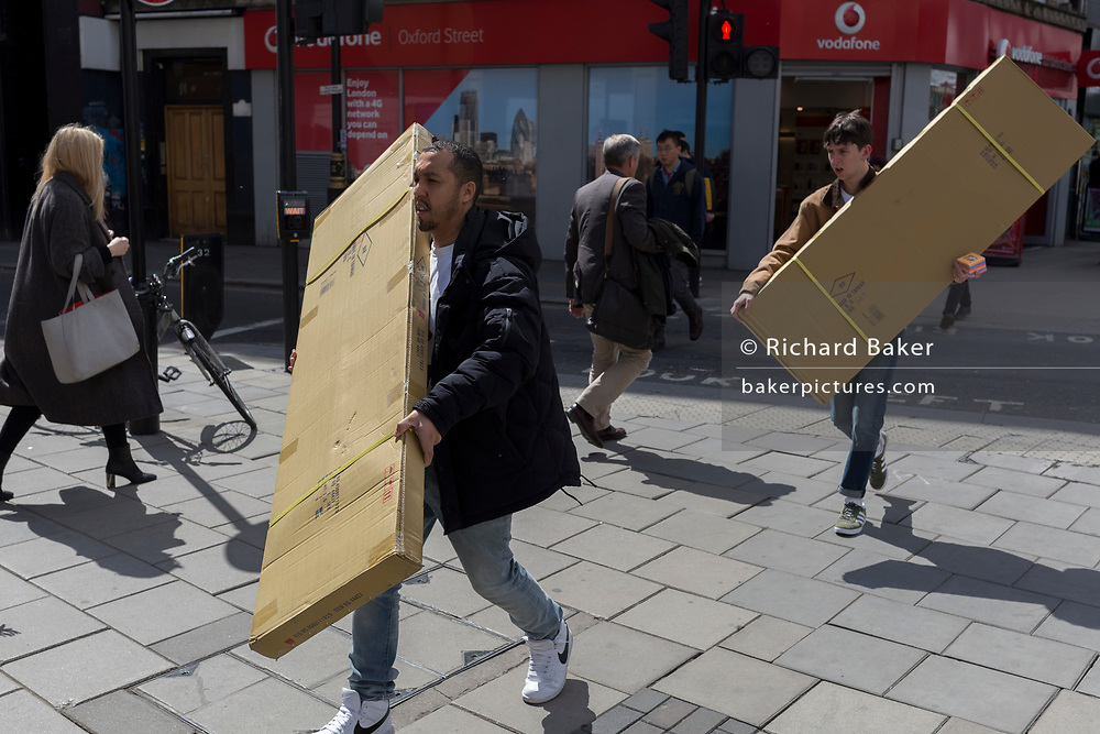 Two men carry awkward, long boxes along Oxford Street, on 1st May, in Trafalgar Square, London, England.