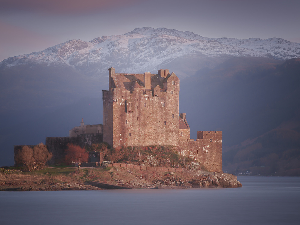 Last rays of the setting sun fall on the castle on Eilean Donan in the western highlands of Scotland.