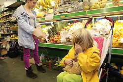 Mother with toddler in buggy shopping for vegetables
