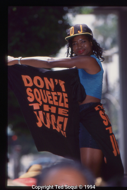 """The OJ Simpson trial and media circus.<br /> A woman holding a """"Don't Squeeze the Juice!"""" tee-shirt,"""