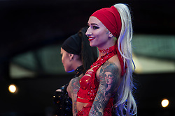Women show off their tattoos during the International tattoo convention at Tobacco Dock in east London.