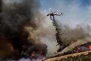 A helicopter makes a slurry drop onto a wildfire, Friday May 31, 2013, near Castiac, California. Fourteen aircraft and more than 550 firefighter were deployed in a ground and air campaign against a brush fire that has blackened about 1,500 acres in sparsely populated San Francisquito Canyon in the Angeles National Forest northeast of Santa Clarita. The Powerhouse Fire, which broke out Thursday afternoon, was about 15 percent contained. The estimated date of full containment is Wednesday, June 5. (Photo by Ringo Chiu/PHOTOFORMULA.com)