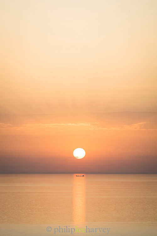 Scenic sunset seascape with silhouette of oil tanker seen from island of Chios, Greece