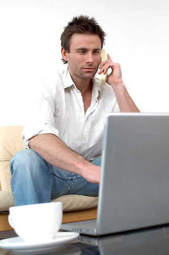 man on sofa working on a laptop computer, internet banking, buying online, home office, working from home<br />