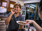 """29 MARCH 2013 - BANGKOK, THAILAND: Saiyuud Diwong """"Poo"""" shares a plate of fried insects, a Thai delicacy, with the students in her cooking class.    PHOTO BY JACK KURTZ"""