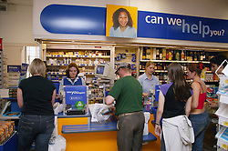 Shop assistants serving customers at checkout in supermarket,
