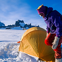 Mike Sharp sets up a tent in Queen Maud Land, Antarctica.  Mt. Ulvetanna and Fenris Mountains in background.