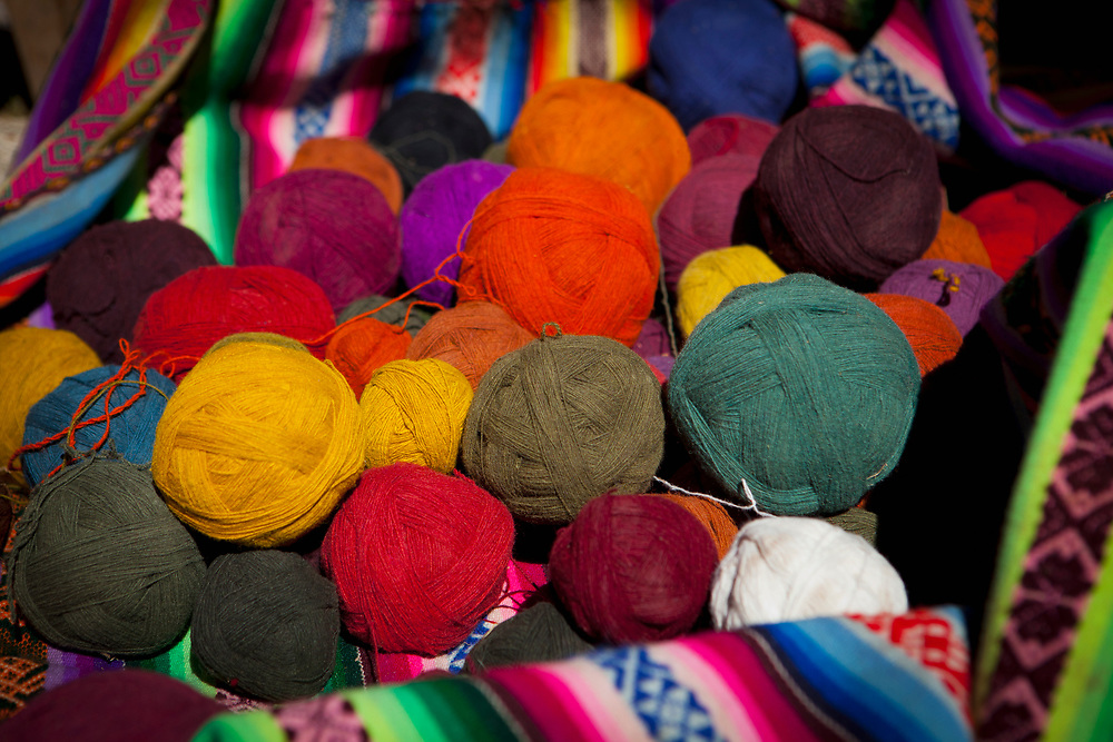 Colorful hand woven balls of dyed Alpaca yarn displayed in a basket